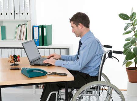 persona en silla de ruedas: hombre en silla de ruedas a su lugar de trabajo