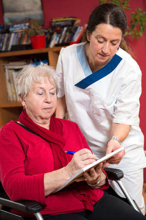 nurse is helping a old woman with a form  photo