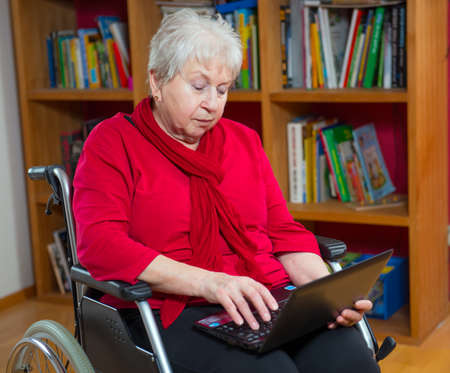 female senior in wheelchair using computer photo
