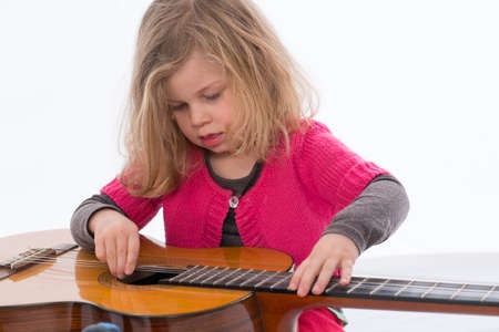 bonny: little girl is playing with a guitar Stock Photo