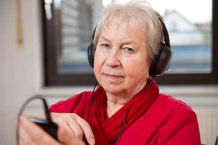 female senior listening music photo