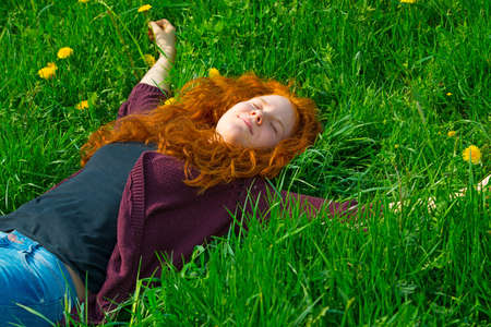 red-haired girl lying on the spring meadow photo
