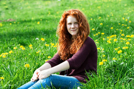 red-haired girl sitting in the spring meadow photo