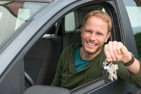 thumb keys: smiling young man in his new car