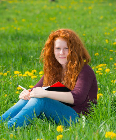 redhaired: red-haired girl in the spring- meadow is reading Stock Photo