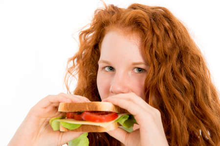red haired girl: red haired girl eating sandwich Stock Photo