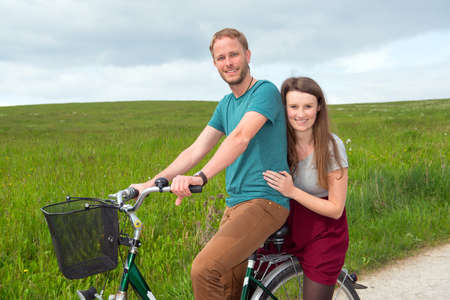 twosome: young man and woman on bicycle