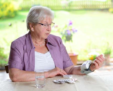 high blood pressure: older woman is measuring blood pressure