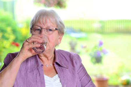 female senior is drinking water Standard-Bild