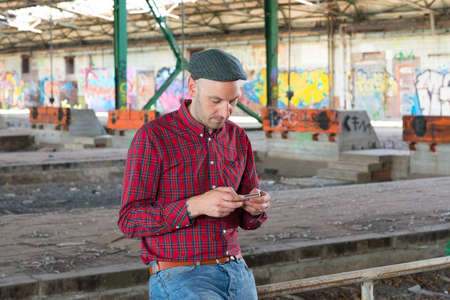 concourse: young man is using smartphone in a old station concourse Stock Photo