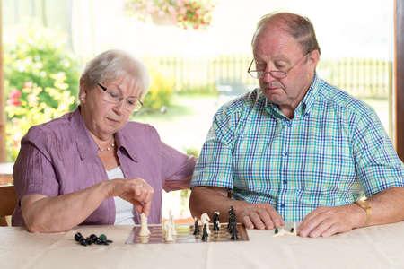 cogitation: senior couple playing chess