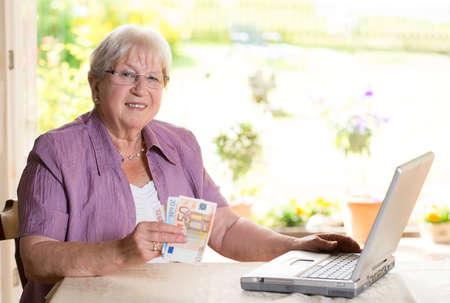 female senior with money is using computer photo