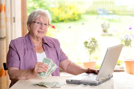 female senior with money is using computer 版權商用圖片 - 34499908