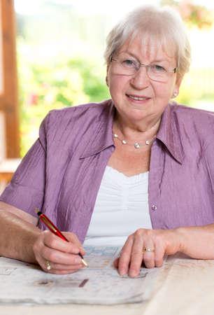 felame senior is solving crossword 版權商用圖片 - 34499914