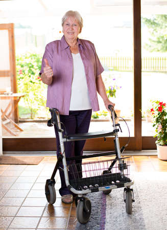 female senieor with walking frame with thumb up