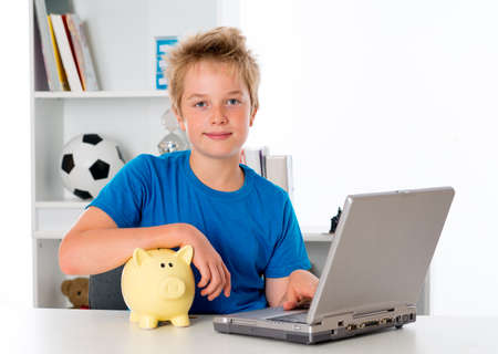 nice boy with laptop and piggy bank