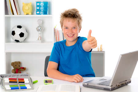 boy is doing homework with book and computer