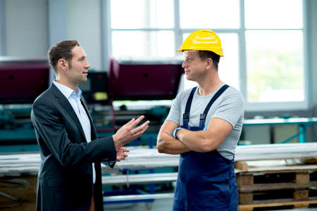 work workman: young boss and worker in conversation Stock Photo