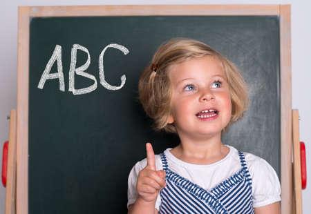finger on trigger: clever girl in front of black board
