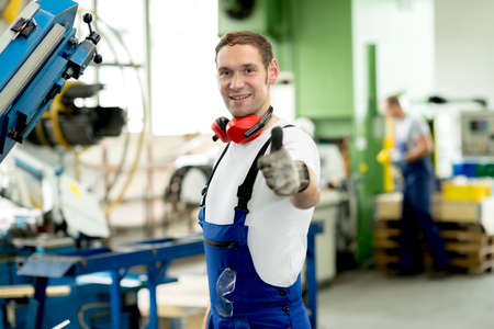 man in factory with thumb up