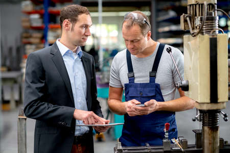 drilling machine: young boss and worker in conversation Stock Photo