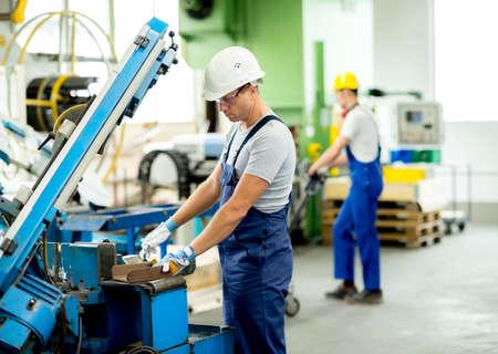 obrero trabajando: trabajador con gafas y casco en la m�quina Foto de archivo