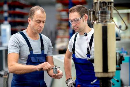 dva dělník v továrně na stroji