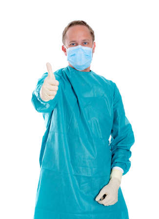 surgical coat: young doctor with surgical mask and green coat with thumb up Stock Photo