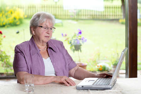 female senior is using computer at home photo