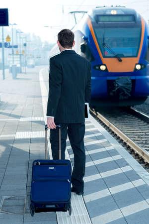 railroad station: businessman in dark suit on railroad station