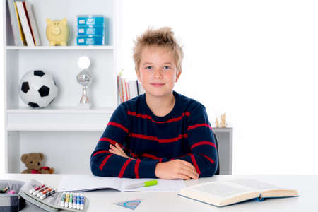 boy is doing homework on writing desk Stock Photo