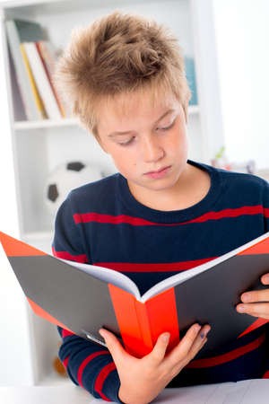 canny: boy with blond hair is reading a book Stock Photo
