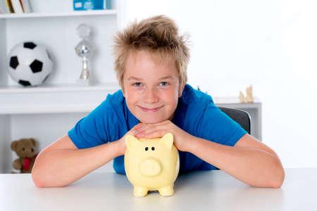 piggybank: smiling boy in blue shirt with piggy-bank
