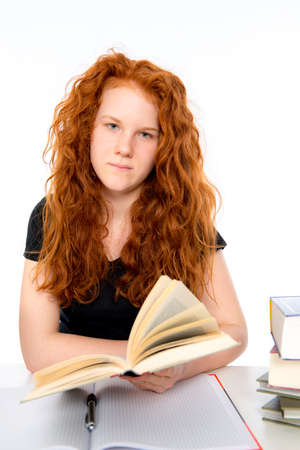 red haired: red haired girl is learning with a book Stock Photo