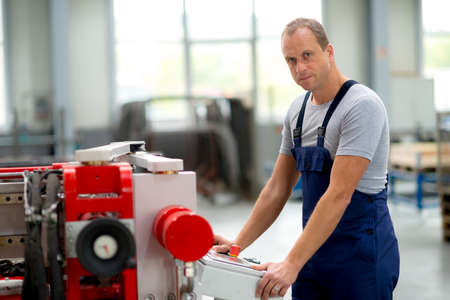 jobholder: young worker in factory using machine Stock Photo