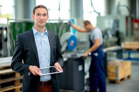 jonge baas met arbe op de achtergrond in zijn fabriek Stockfoto