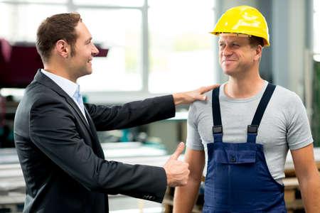 supervisores: joven jefe se elogiaba trabajador en la fábrica Foto de archivo