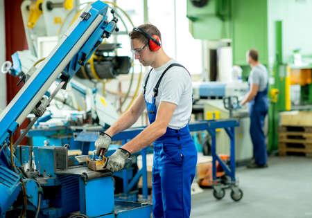 mecanica industrial: trabajador en la ropa de protecci�n en f�brica utilizando m�quina Foto de archivo