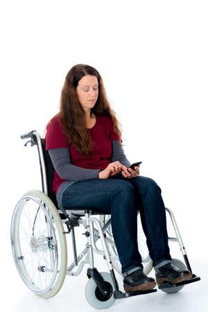 paraplegico: mujer joven en silla de ruedas utilizando su tel�fono inteligente
