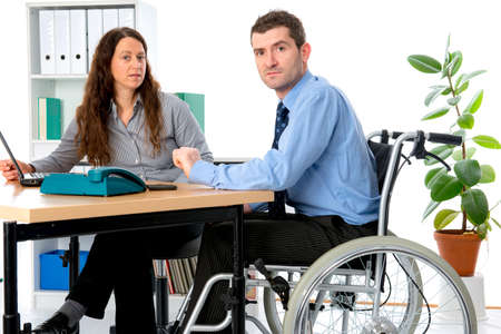 man in wheelchair and his  is female colleague working in the office photo