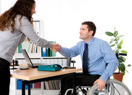 discapacidad: hombre en silla de ruedas est� saludando a una mujer en la oficina