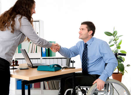 man in wheelchair is greeting a woman in the office