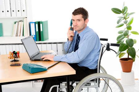 paraplegico: hombre en silla de ruedas est� trabajando en la oficina Foto de archivo