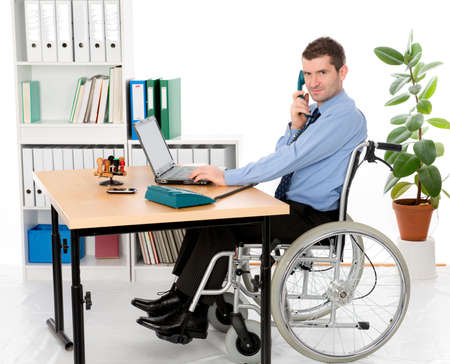 man in wheelchair is working in the office photo