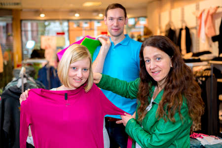 two women and a man in the clothes shop looking for outfit photo