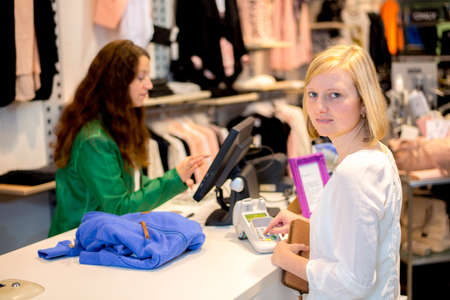 young woman in the clothes shop over the counter photo