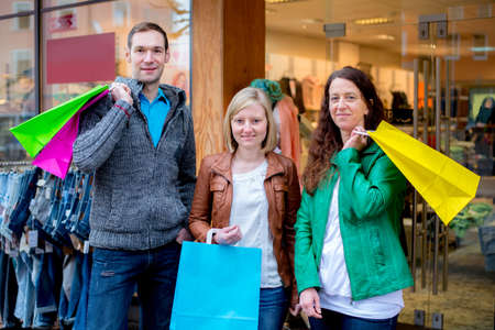 two women and a man in front of clothes shop photo