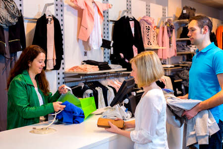 over the counter: young woman and man in the clothes shop over the counter