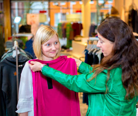 two women in the clothes shop looking for outfit photo