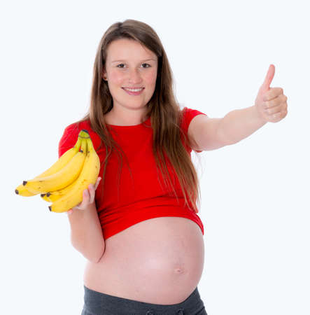 young pregnant woman with bananas and thumb up in front of white background photo